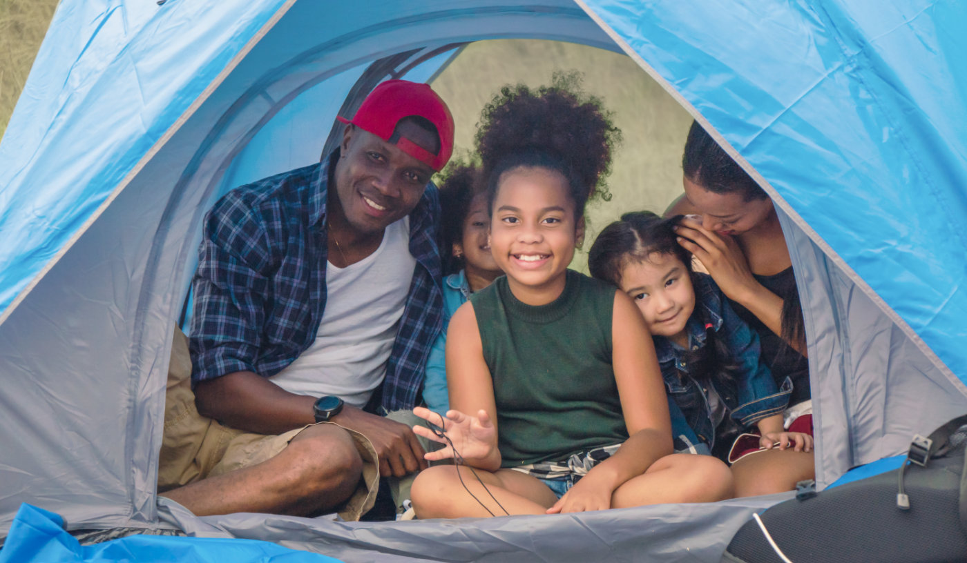 african american family, parent with kids, and asian adopted child having fun together in camping at natural park